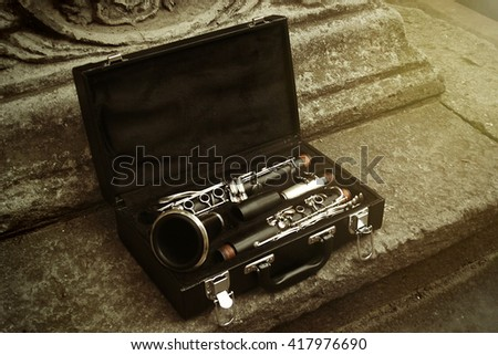 beautiful black and silver clarinet in classic case on background of old city, space for text - stock photo
