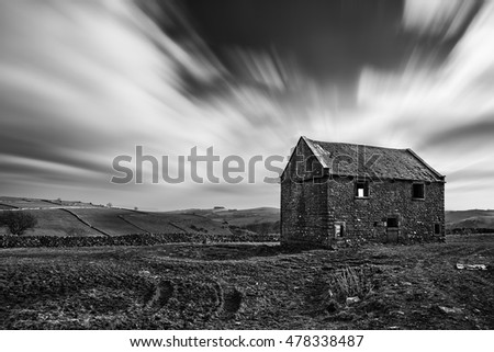 Beautiful black and white landscape of derelict barn in field