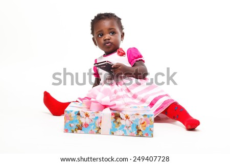 Beautiful black baby girl isolated in white with a gift