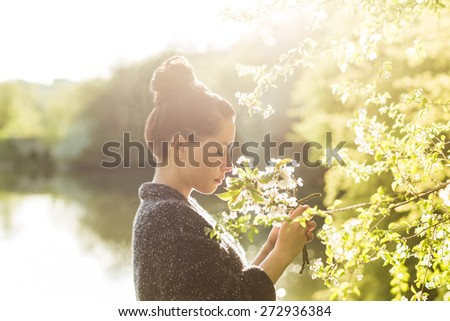 Beautiful black hair woman enjoying blooming tree from profile, pretty girl relaxing outdoor.  Happy young lady and spring green nature. Low depth of field. Strong back light. - stock photo