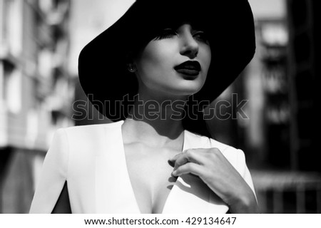 beautiful black haired indian woman poses in backyard of  bis city high-rise. It has green lawn and many concrete structures. Portrait is lit with spring sun. Lady is wearing white dress, felt hat.