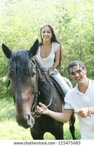 beautiful black stallion in a field with young couple