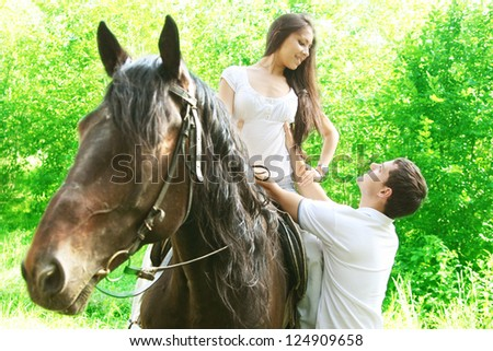 beautiful black stallion in a green forest with young  latin hispanic couple - stock photo