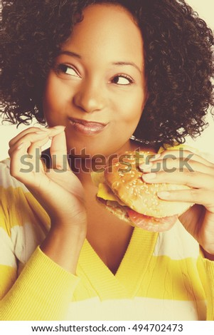 Beautiful black woman eating burger sandwich