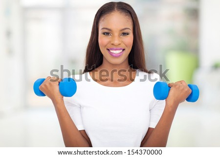 beautiful black woman exercising with dumbbells - stock photo