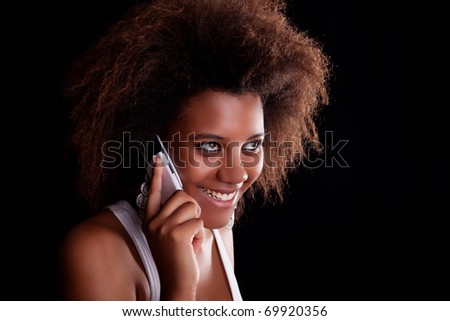 Beautiful black woman happy on the phone, isolated on black background. Studio shot. - stock photo