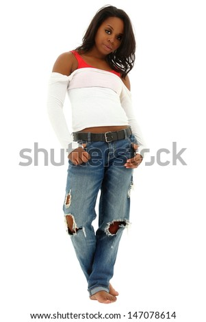 Beautiful black woman in torn jeans and white shirt standing on white floor. Clipping path. - stock photo