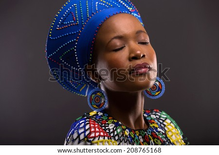 beautiful black woman in traditional clothes with eyes closed - stock photo