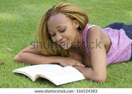 Beautiful black woman lying on the grass reading a book