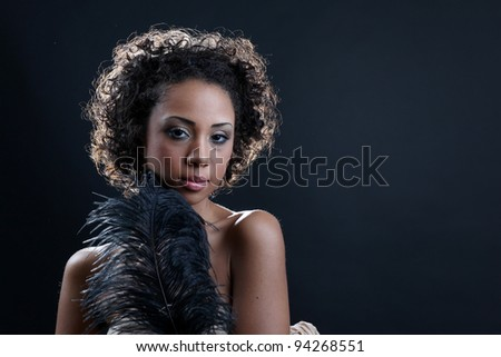 Beautiful black woman posing in a studio playing with a black feather.