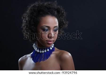 Beautiful black woman posing in a studio wearing a blue necklace.