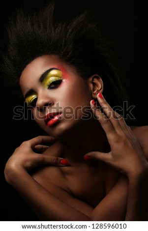 Beautiful black woman with glossy makeup isolated over black background - stock photo