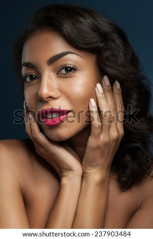 Beautiful black  woman with long thick shiny hair, with hand near face - stock photo