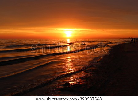 Beautiful blazing sunset landscape at black sea and orange sky above it with awesome sun golden reflection on calm waves as a background. Amazing summer sunset view on the beach. Russian nature, Sochi - stock photo