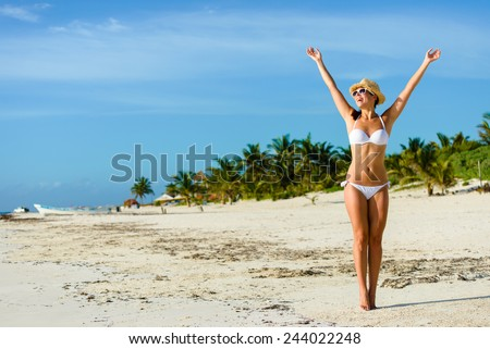 Beautiful blissful woman in white bikini enjoying tropical beach and caribbean summer vacation. Tanned brunette raising arms and enjoying freedom by the sea at Playa Paraiso, Riviera Maya, Mexico. - stock photo