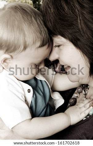 Beautiful blond baby boy sitting by his grandmother - stock photo