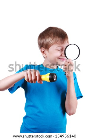 Beautiful blond boy in a in a blue t-shirt holds a flashlight and a magnifying glass looking having found something interesting  - stock photo