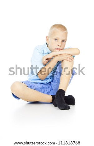 beautiful blond boy sits isolated on a white background