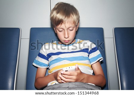 Beautiful blond boy wearing a colorful t-shirt sitting in an airport terminal typing an sms on a mobile phone - stock photo