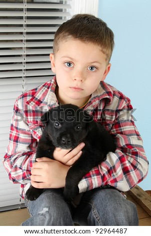 Beautiful blond boy with a black puppy - stock photo