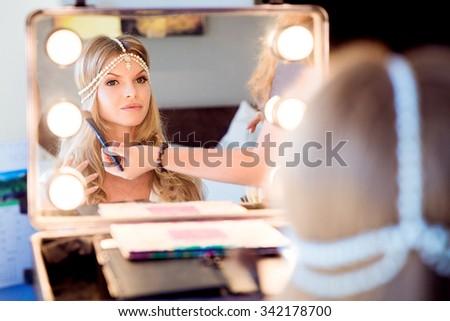 Beautiful blond bride doing makeup in her wedding day near mirror. Bride makeup. - stock photo