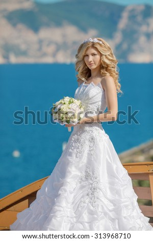 Beautiful blond bride in wedding dress with bouquet of flowers over sea, mountains and blue sky background. Landscape.  - stock photo