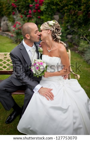 Beautiful blond bride kissing handsome groom sitting on the bench in the garden with red roses.Happy, hugging, just married.