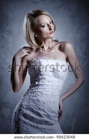 Beautiful blond bride posing indoors - stock photo