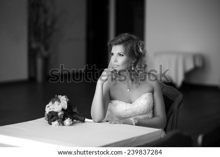 Beautiful blond bride seats at white table or piano, is ready for a new bright life, inside interior. Big bouquet is lying on the table near her elbow. Wedding dress white veil Pretty young woman love - stock photo