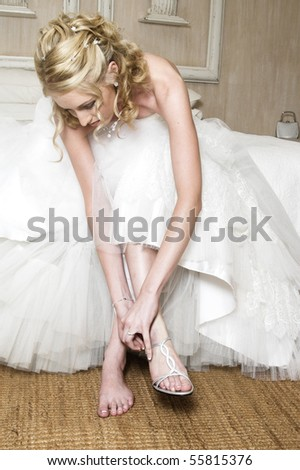 Beautiful Blond bride wearing diamond jewelery and a white gown - stock photo