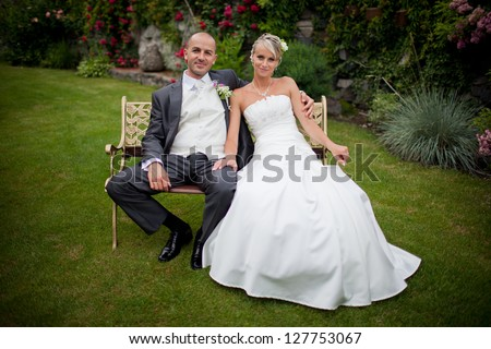 Beautiful blond bride with smiling handsome groom sitting on the bench in the garden with red roses.Happy, laughing, just married.