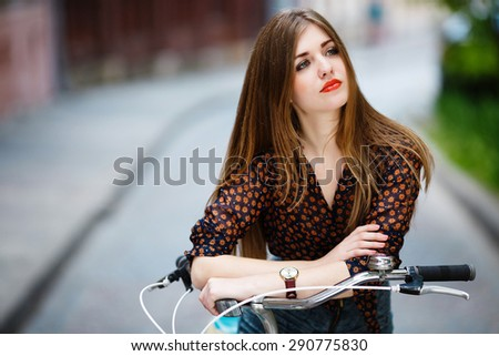 Beautiful blond-brown girl with bicycle, wearing shirt. Thinking. On street background. - stock photo