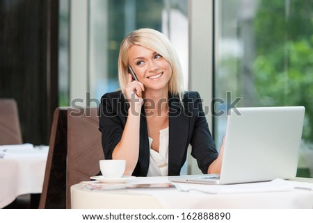 Beautiful blond businesswoman talking by phone. While sitting at caf���© with laptop  - stock photo