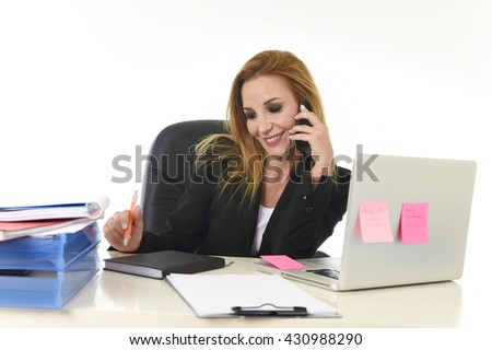 beautiful blond businesswoman talking on mobile phone smiling holding pen writing notes on notepad folder happy and confident in communication concept working at laptop computer office desk - stock photo