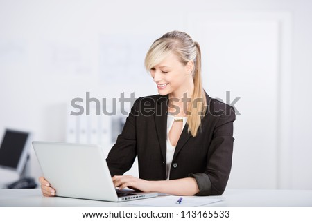 Beautiful blond businesswoman working in front of laptop