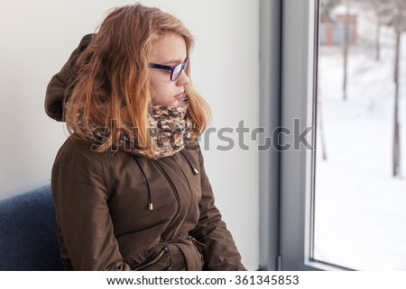 Beautiful blond Caucasian teenage girl in glasses and warm outwear sitting on blue sofa near winter window