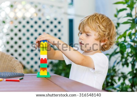 Beautiful blond child playing with lots of colorful plastic blocks indoor. Active kid boy having fun with building and creating - stock photo