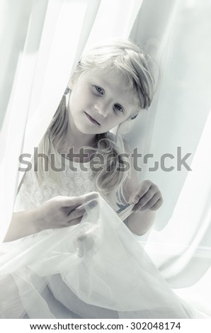beautiful blond child with long hair among white curtain - stock photo