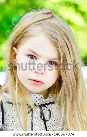 Beautiful blond crying little girl with tears on her cheeks - stock photo