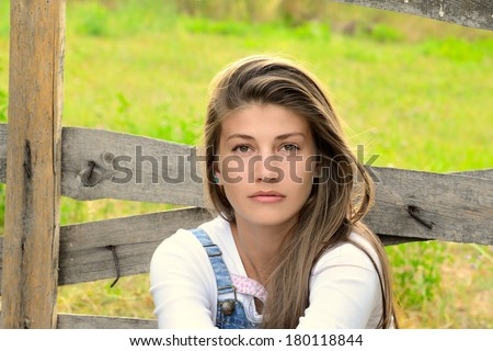 Beautiful Blond Farm Girl Standing Next To Old Wooden Fence