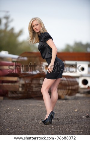 Beautiful blond fashion model with her hands on her hip and her head tilted up, wearing a short black skirt posing at a construction site outdoors. - stock photo