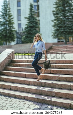 Beautiful blond female business woman walks in city park on stairs- carrying brief case over arm and talking on cell phone against summer trees - stock photo