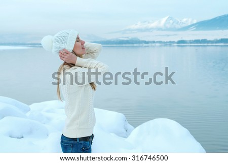 Beautiful blond female in winter hat, stay near the mountains lake.