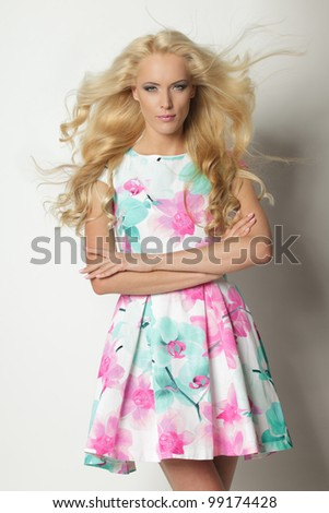 Beautiful blond female posing in summer dress with hairs lightly fluttering on the wind - stock photo