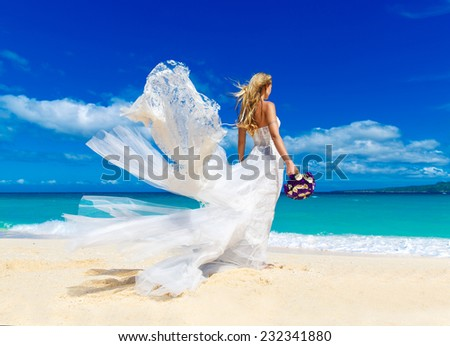 beautiful blond fiancee in white wedding dress with big long white train and with wedding bouquet stand on shore sea - stock photo
