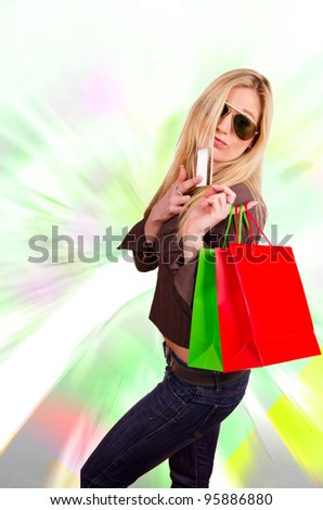 Beautiful blond girl buyer with credit card and shopping bags