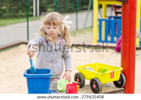 beautiful blond girl child playing on the playground