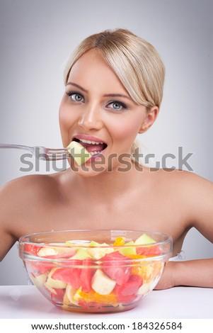 Beautiful blond girl eating fruit salad - stock photo