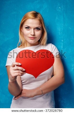 Beautiful blond girl holds in the hand a big red heart on the blue backgroung. - stock photo