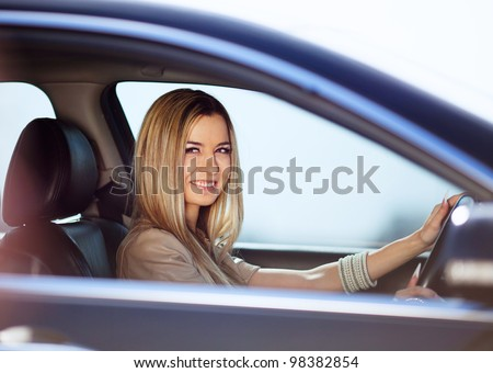 Beautiful blond girl in her car - stock photo